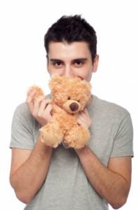 Man cuddling teddy bear