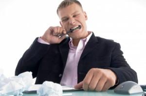 Man biting pen